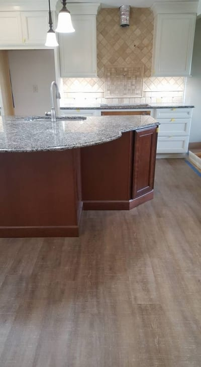A recently remodeled kitchen with rustic wood flooring
