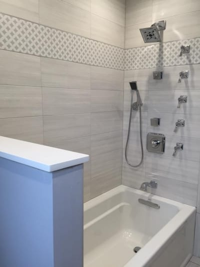 Intricately designed wall tiles around a bath and shower combo
