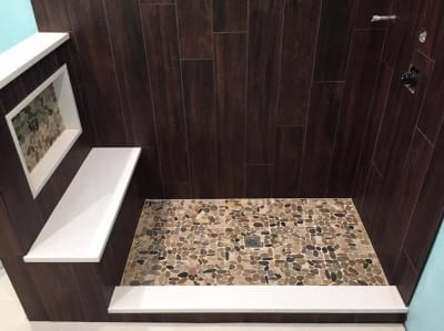 Stone and concrete flooring with dark wooden panel ling on the walls of an open shower