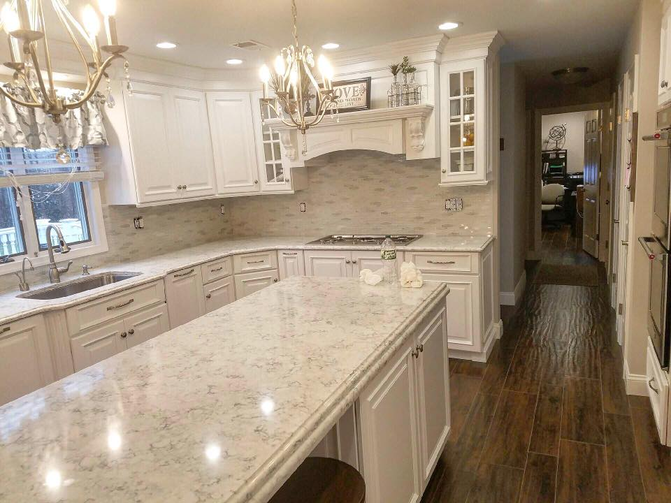 A recently remodeled kitchen with a ceramic wall pattern behind a marble kitchen counter