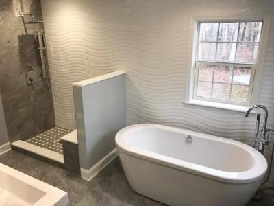 Intricate plaster wall pattern in bathroom behind bath and open shower