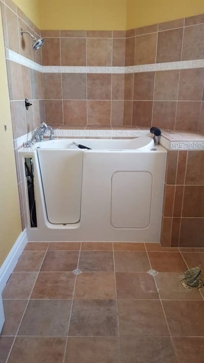 Ceramic wall and floor tiles around an accessible bathtub