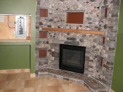 Stonework and concrete accent around a fireplace