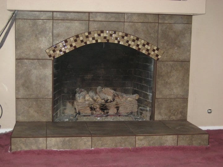 A fireplace with marble tiles around it
