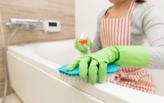 Women scrubbing bathtub to prevent mold